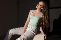 Mulher bonita com composição e penteado que senta-se na roupa brilhante foto de stock