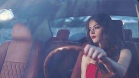 A mulher bonita com composição em sua cara está no carro e olha a estrada vídeos de arquivo