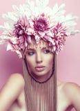 Mulher bonita com coroa da flor e composição no fundo cor-de-rosa foto de stock royalty free