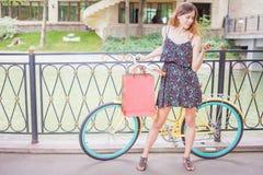 Mulher bonita com erros usando o telefone celular perto da bicicleta do vintage Fotografia de Stock Royalty Free
