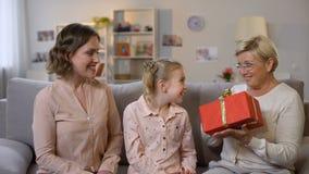 Mulher bonita com a filha que apresenta a caixa de presente agradável à avó, aniversário video estoque