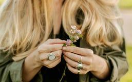 Mulher bonita com a flor longa da terra arrendada do cabelo Mãos com os acessórios à moda do boho dos anéis Nenhum foco foto de stock royalty free