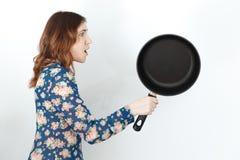 A mulher bonita com frigideira, humor o 8 de março foto de stock
