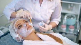 Mulher bonita com máscara facial no salão de beleza vídeos de arquivo