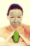 Mulher bonita com a máscara facial que guarda o abacate Fotos de Stock