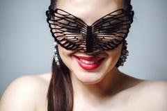 Mulher bonita com máscara preta do laço sobre seus olhos Close up 'sexy' vermelho dos bordos e dos pregos imagem de stock