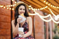 A mulher bonita com o cabelo escuro, brilhando eyes eatting com o croissant saboroso do prazer e café afastado bebendo ao sentar- foto de stock
