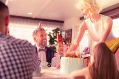 Mulher bonita com o cabelo ondulado que põe o bolo de aniversário para o filho imagem de stock