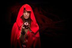 Mulher bonita com o casaco vermelho que guarda a maçã Fotografia de Stock Royalty Free