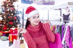 Mulher bonita com o chapéu de Santa na loja de roupa Imagens de Stock