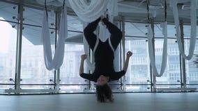 Mulher bonita com o corpo atrativo que faz a ioga a?rea antigravitante na rede, executando o exerc?cio antigravitante da ioga den vídeos de arquivo