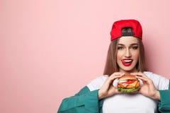 Mulher bonita com o hamburguer saboroso no fundo da cor foto de stock royalty free