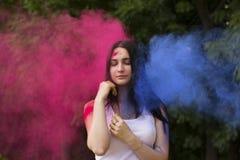 Mulher bonita com o pó colorido que explode em torno dela imagens de stock royalty free