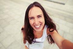 Mulher bonita com o sorriso ingênuo que faz um selfie Foto de Stock Royalty Free