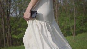 Mulher bonita com o telefone celular na saia e no revestimento brancos longos das calças de brim que anda com o fim da floresta a filme