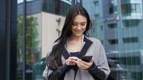 Mulher bonita com o telefone perto do centro de negócio vídeos de arquivo