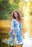 Mulher bonita com o vestido medieval longo que está na água Fotos de Stock Royalty Free