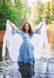 Mulher bonita com o vestido medieval longo que está na água Fotografia de Stock Royalty Free
