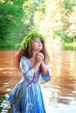 Mulher bonita com o vestido medieval longo que reza na água Imagens de Stock