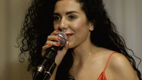 Mulher bonita com os bordos vermelhos com microfone filme