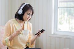 Mulher bonita com os fones de ouvido e o smartphone que relaxam sobre fotos de stock