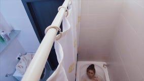 Mulher bonita com os fones de ouvido no banho Mulher que escuta a música no banho de espuma video estoque