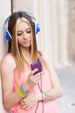 Mulher bonita com os hearphones que olham o telefone esperto, vida moderna imagem de stock royalty free