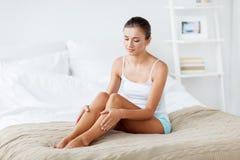 Mulher bonita com pés desencapados na cama em casa Foto de Stock Royalty Free