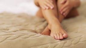 Mulher bonita com pés desencapados na cama em casa vídeos de arquivo