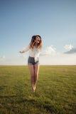 Mulher bonita com pés 'sexy' e o short da sarja de Nimes que salta na grama, sapata menos Fotografia de Stock Royalty Free