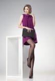 A mulher bonita com pés 'sexy' longos em meias do às bolinhas vestiu o levantamento elegante fotografia de stock