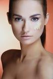 Mulher bonita com pele fresca da saúde com creme fêmea da composição em sua face Fotos de Stock