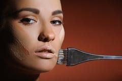 Mulher bonita com a pele fresca da saúde que aplica o creme fêmea da composição Imagens de Stock Royalty Free
