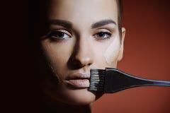 Mulher bonita com a pele fresca da saúde que aplica o creme fêmea da composição nos bordos Fotografia de Stock