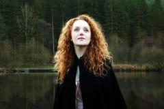 Mulher bonita com por muito tempo conexão em cascata do cabelo vermelho que olha acima Fotografia de Stock Royalty Free