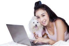 Mulher bonita com portátil e cão na cama fotos de stock royalty free