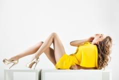 A mulher bonita com pés 'sexy' longos vestiu o levantamento elegante no estúdio - corpo completo Foto de Stock