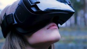 Mulher bonita com realidade virtual no parque exterior Dispositivo dos vidros dos auriculares de VR Jovem mulher em vidros de um  Imagens de Stock