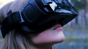 Mulher bonita com realidade virtual no parque exterior Dispositivo dos vidros dos auriculares de VR Jovem mulher em vidros de um  Foto de Stock