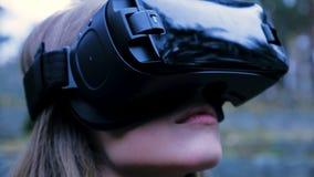 Mulher bonita com realidade virtual no parque exterior Dispositivo dos vidros dos auriculares de VR Jovem mulher em vidros de um  Imagem de Stock