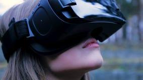 Mulher bonita com realidade virtual no parque exterior Dispositivo dos vidros dos auriculares de VR Jovem mulher em vidros de um  Fotografia de Stock