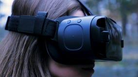Mulher bonita com realidade virtual no parque exterior Dispositivo dos vidros dos auriculares de VR Jovem mulher em vidros de um  Foto de Stock Royalty Free