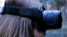 Mulher bonita com realidade virtual no parque exterior Dispositivo dos vidros dos auriculares de VR Jovem mulher em vidros de um  Imagem de Stock Royalty Free