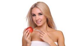 A mulher bonita com a seringa da dose vacinal vermelha injeta na maçã Foto de Stock