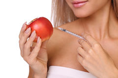 A mulher bonita com a seringa da dose vacinal vermelha injeta na maçã Foto de Stock Royalty Free