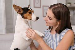 Mulher bonita com seu cão que senta-se no sofá imagem de stock royalty free