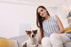 Mulher bonita com seu cão que senta-se no sofá fotografia de stock