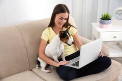 Mulher bonita com seu cão que trabalha no portátil imagens de stock