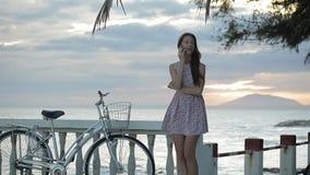 Mulher bonita com telefone celular em uma praia rochosa no por do sol filme
