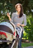 Mulher bonita com transporte de bebê usando a pilha fotografia de stock